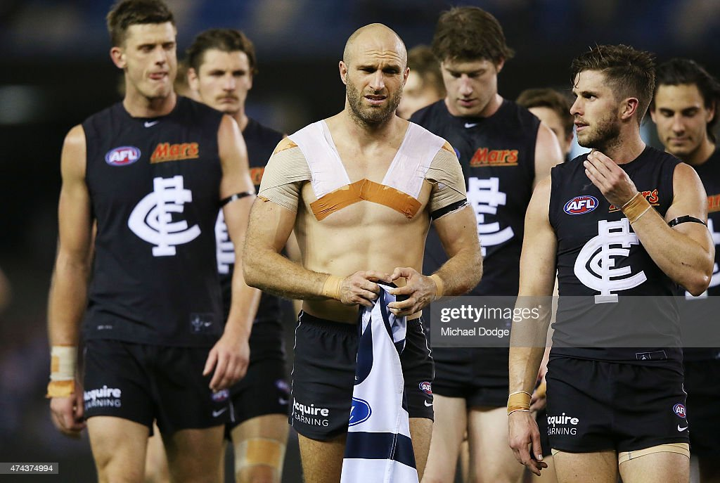 Marc Murphy of the Blues (R) and Chris Judd (C) of the Blues walks off after defeat with the jumper of Cameron Guthrie of the Cats during the round eight AFL match between the Geelong Cats and the Carlton Blues at Etihad Stadium on May 22, 2015 in Melbourne, Australia.