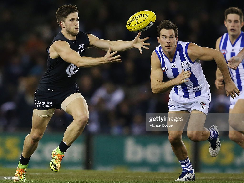 Marc Murphy of the Blues gathers the ball from Levi Greenwood of the Kangaroos during the round 18 AFL match between the Carlton Blues and the North Melbourne Kangaroos at Etihad Stadium on July 18, 2014 in Melbourne, Australia.