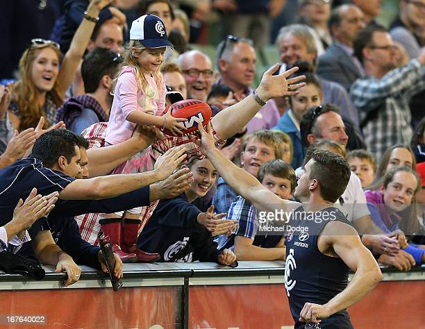 Marc Murphy of the Blues gives a fan a football after their win during the round five AFL match between the Carlton Blues and the Adelaide Crows at...