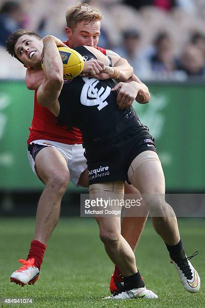 Marc Murphy of the Blues is tackled by Bernie Vince of the Demons during the round 21 AFL match between the Carlton Blues and the Melbourne Demons at...