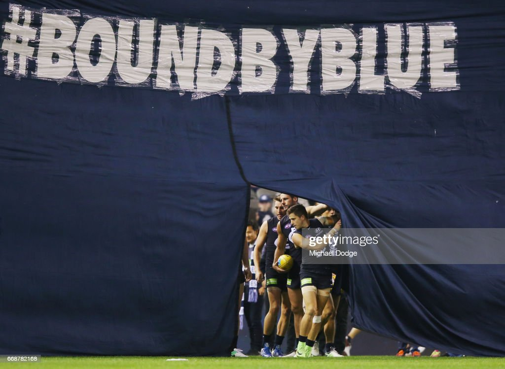 Marc Murphy of the Bluesleads the team out through the banner during the round four AFL match between the Carlton Blues and the Gold Coast Suns at Etihad Stadium on April 15, 2017 in Melbourne, Australia.