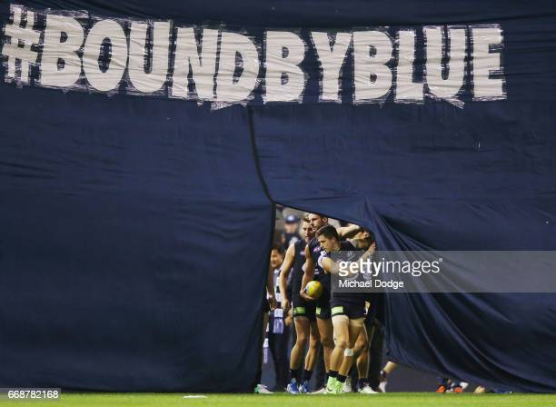 Marc Murphy of the Bluesleads the team out through the banner during the round four AFL match between the Carlton Blues and the Gold Coast Suns at...