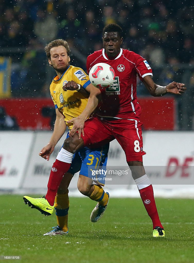 Marc Pfitzner (L) of Braunschweig and Mohamadou Idrissou (R) of Kaiserslautern battle for the ball during the second Bundesliga match between Eintracht Braunschweig and 1. FC Kaiserslautern at Eintracht Stadium on March 11, 2013 in Braunschweig, Germany.