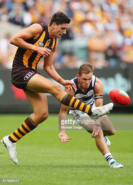 Marc Pittonet of the Hawks kicks the ball off the ground dangerously near the head of Joel Selwood of the Cats during the round one AFL match between...