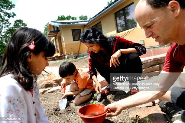 """Marc Plinke, along with his wife Rohini Kanniganti and their two children Sitha Plinke and Roan Plinke plant mint outside of their """"green"""" home in..."""