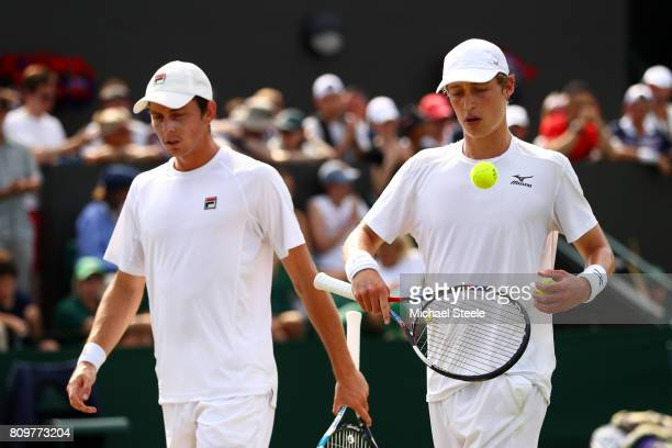 Marc Polmans of Australia and Andrew Whittington of Australia look on during the Gentlemen's Doubles first round match against Bob Bryan of the...