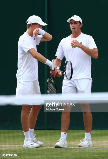 Marc Polmans of Australia and Andrew Whittington of Australia speak during the Gentlemen's Doubles first round match against Bob Bryan of the United...