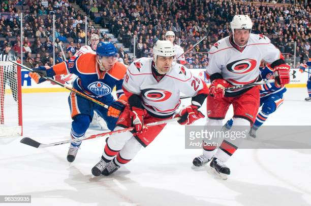 Marc Pouliot of the Edmonton Oilers Tom Kostopoulos and Aaron Ward of the Carolina Hurricanes watch the puck go into the corner at Rexall Place on...