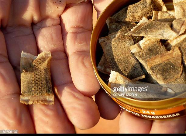 Marc PREEL A woman shows portions of snus, a moist powder tobacco product that is consumed by placing it under the lip, in Stockholm on August 6,...