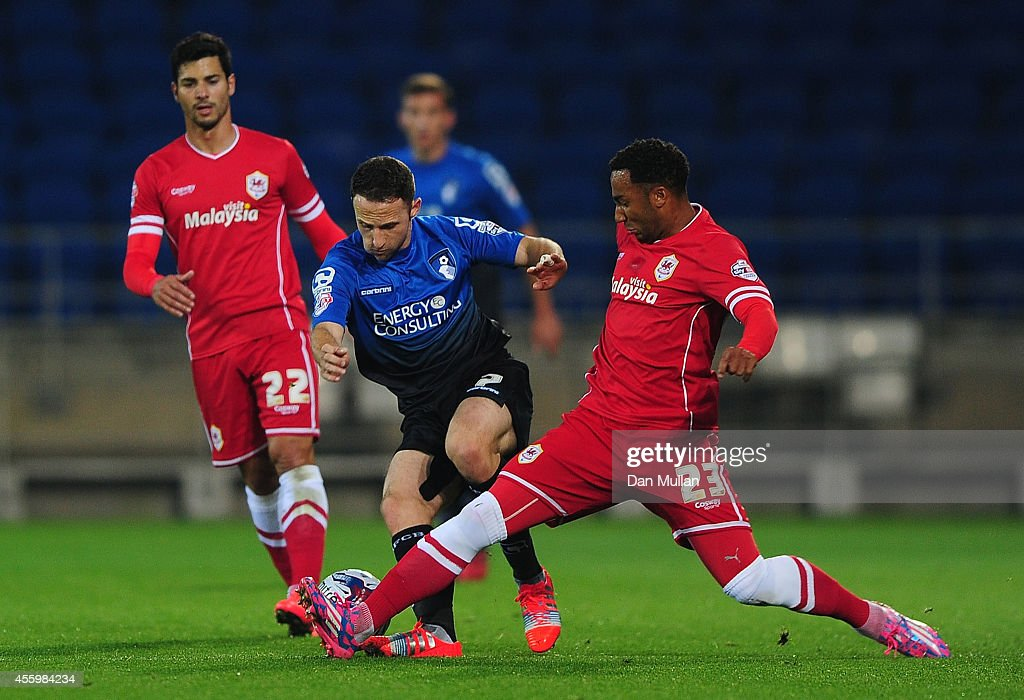 Marc Pugh of Bournemouth is tackled by Nicky Maynard of Cardiff City during the Capital One Cup third round match between Cardiff City and Bournemouth at Cardiff City Stadium on September 23, 2014 in Cardiff, Wales.