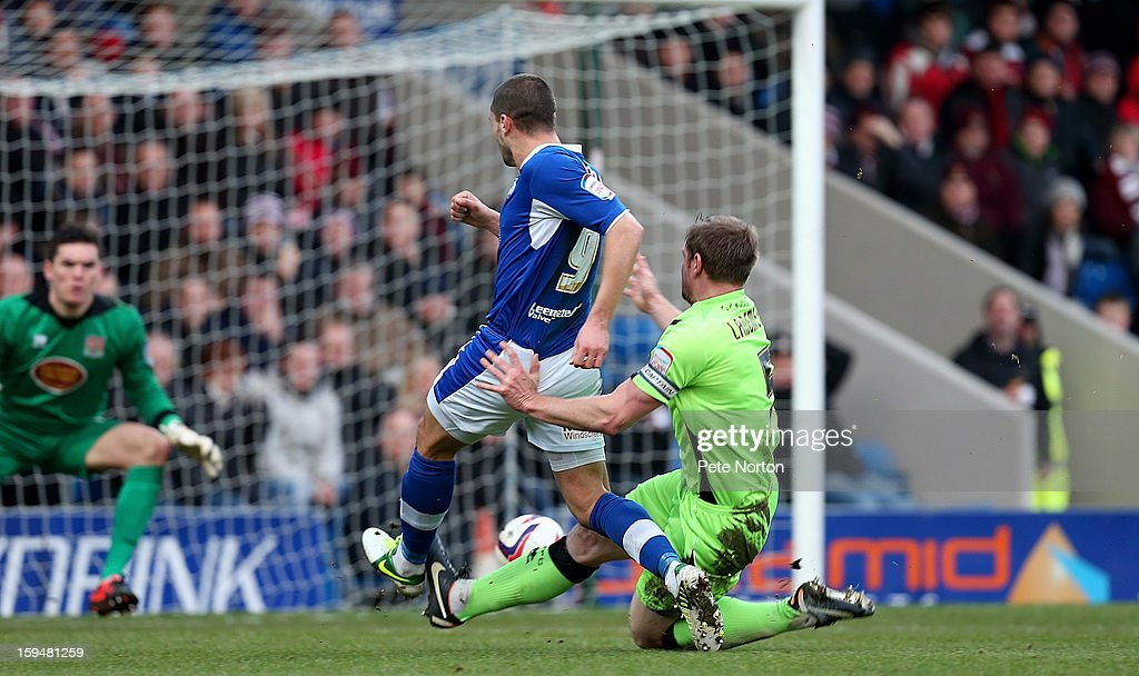 Marc Richards of Chesterfield fires in a shot under pressure from Kelvin Langmead of Northampton Town to score his 2nd and his sides 3rd goal during the npower League Two match between Chesterfield and Northampton Town at the Proact Srtadium on January 12, 2013 in Chesterfield, England.