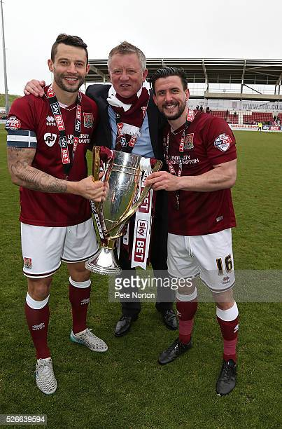 Marc Richards,David Buchanan and manager Chris Wilder of Northampton Town celebrate with the Sky Bet League Two champions trophy after the Sky Bet...