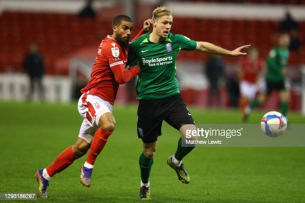 Marc Roberts of Birmingham City is challenged by Lewis Grabban of Nottingham Forest during the Sky Bet Championship match between Nottingham Forest...