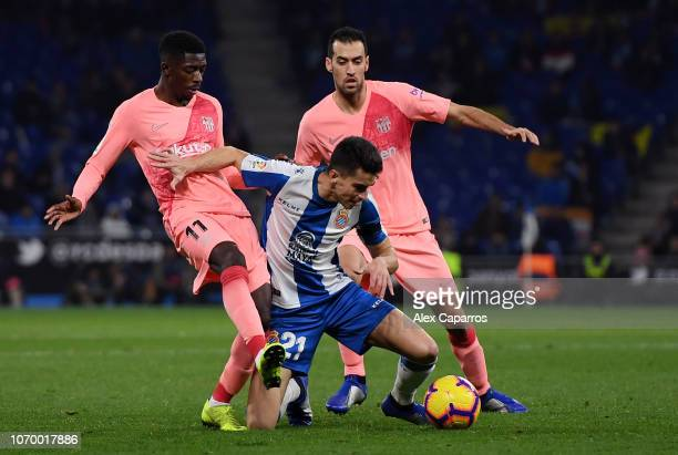 Marc Roca of RCD Espanyol is challenged by Ousmane Dembele of Barcelona and Sergio Busquets of Barcelona during the La Liga match between RCD...