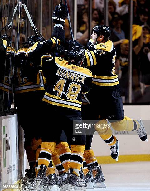 Marc Savard of the Boston Bruins is swarmed by teamamtes Matt Hunwick and Steve Begin after Savard scored the game winning goal in overtime against...