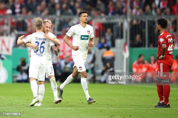 Marc Schnatterer of Heidenheim celebrates his team's second goal with team mate Niklas Dorsch during the DFB Cup quarterfinal match between Bayern...