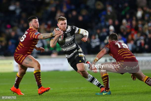 Marc Sneyd of Hull FC attempts to run past Oliver Roberts and Daniel Smith of Huddersfield Giants during the BetFred Super League match between Hull...
