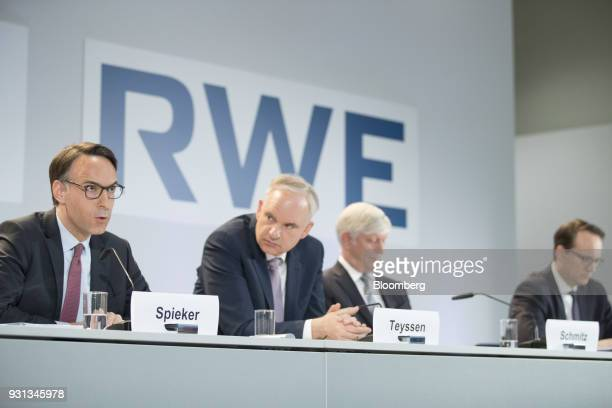 Marc Spieker chief financial officer of EON SE left speaks as he sits beside Johannes Teyssen chief executive officer of EON SE Rolf Schmitz chief...