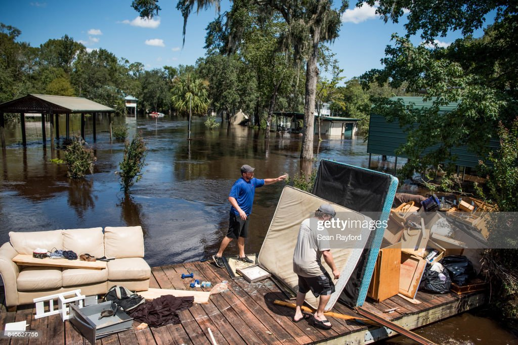 Marc St. Peter, left, and Chris Wisor lend a hand cleaning up as floodwaters from Hurricane Irma recede September 13, 2017 in Middleburg, Florida. Flooding in town from the Black Creek topped the previous high water mark by about seven feet and water entered the second story of many homes.