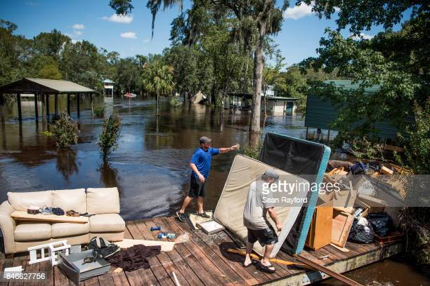 Marc St Peter left and Chris Wisor lend a hand cleaning up as floodwaters from Hurricane Irma recede September 13 2017 in Middleburg Florida Flooding...