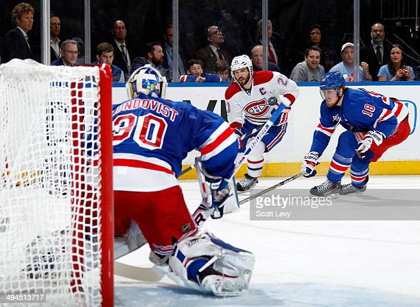 Marc Staal and Henrik Lundqvist of the New York Rangers and Brian Gionta of the Montreal Canadiens watch a loose puck in the second period of Game...