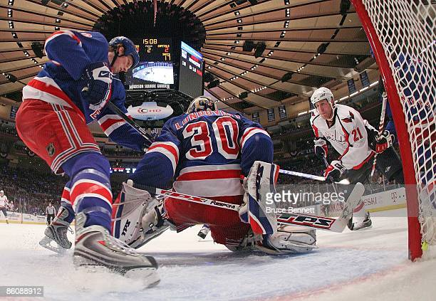 Marc Staal and Henrik Lundqvist of the New York Rangers defend the net against Brooks Laich of the Washington Capitals during Game Three of the...