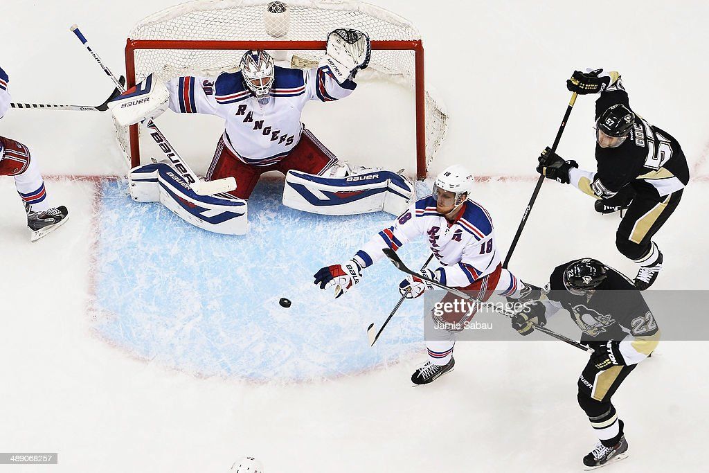 Marc Staal #18 of the New York Rangers bats down a loose puck in front of goaltender Henrik Lundqvist #30 of the New York Rangers as Lee Stempniak #22 of the Pittsburgh Penguins and Marcel Goc #57 of the Pittsburgh Penguins skate by in the third period in Game Five of the Second Round of the 2014 NHL Stanley Cup Playoffs on May 9, 2014 at CONSOL Energy Center in Pittsburgh, Pennsylvania.New York defeated Pittsburgh 5-1.