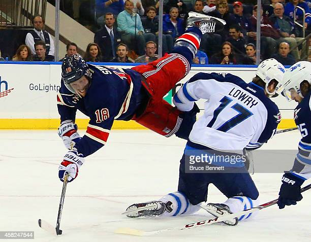 Marc Staal of the New York Rangers gets the second period shot off as he is flipped by Adam Lowry of the Winnipeg Jets at Madison Square Garden on...