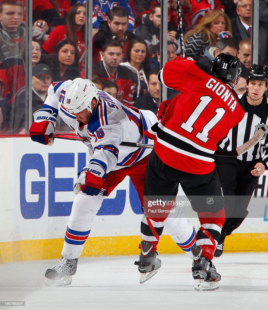 Marc Staal #18 of the New York Rangers is checked by Stephen Gionta #11 of the New Jersey Devils during the third period of an NHL hockey game at Prudential Center on February 5, 2013 in Newark, New Jersey.