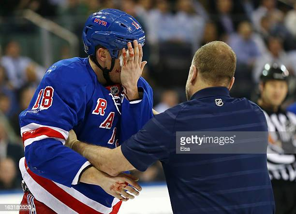 Marc Staal of the New York Rangers is helped off the ice after he was hit in the face with a puck in the third period against the Philadelphia Flyers...