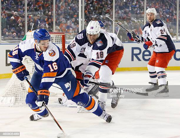 Marc Staal of the New York Rangers pushes Peter Regin of the New York Islanders away from the crease during the 2014 Coors Light NHL Stadium Series...