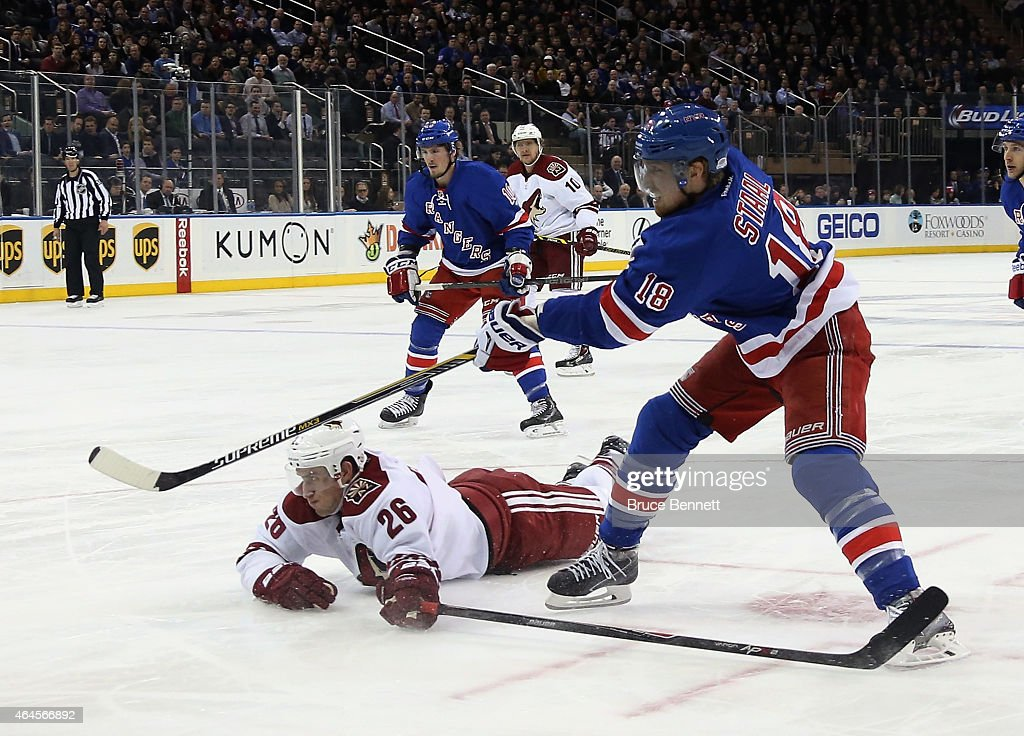 Marc Staal #18 of the New York Rangers shoots the puck past a sliding Michael Stone #26 of the Arizona Coyotes at Madison Square Garden on February 26, 2015 in New York City. The Rangers defeated the Coyotes 4-3.