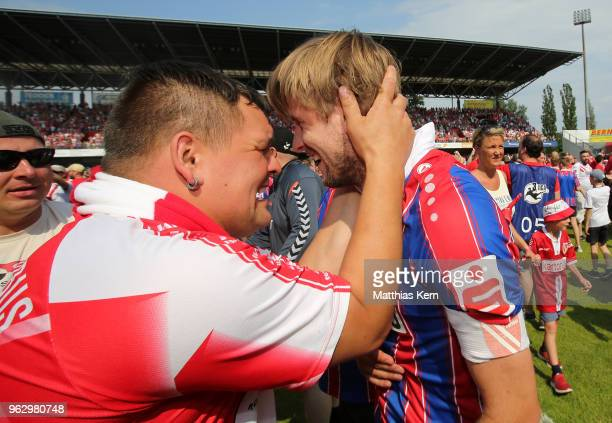 Marc Stein of Cottbus celebrates with supporters after moving up into the third league after the Third League Playoff Leg 2 match between FC Energie...