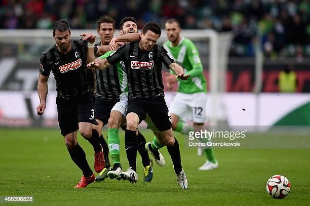 Marc Torrejon and Sascha Riether of SC Freiburg challenge Daniel Caligiuri of VfL Wolfsburg during the Bundesliga match between VfL Wolfsburg and SC...