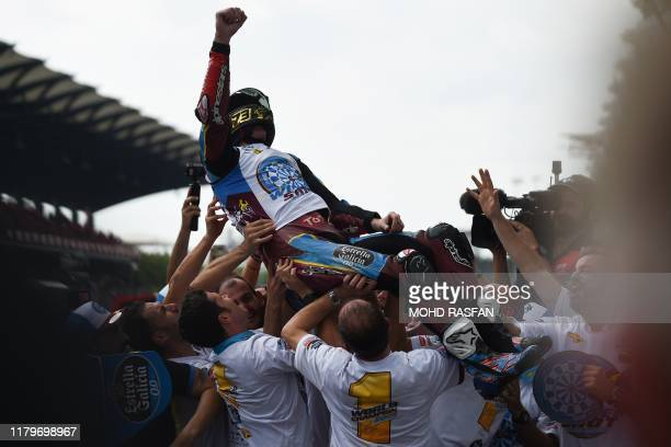 Marc VDS's Spanish rider Alex Marquez celebrates with his team after becoming Moto2 world champion following the Moto2-class Malaysian Grand Prix...