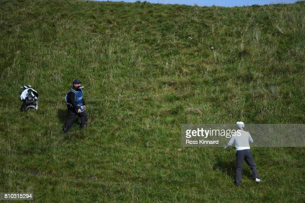 Marc Warren of Scotland exchanges clubs with his caddie on the 9th hole during day two of the Dubai Duty Free Irish Open at Portstewart Golf Club on...