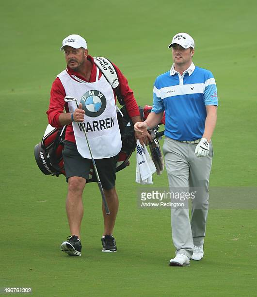 Marc Warren of Scotland walks with his caddie Ken Herring on the ninth hole during the first round of the BMW Masters at Lake Malaren Golf Club on...