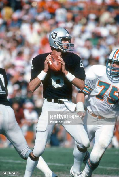 Marc Wilson of the Oakland Raiders drops back to pass against the Miami Dolphins during an NFL football game November 15 1981 at the Orange Bowl in...