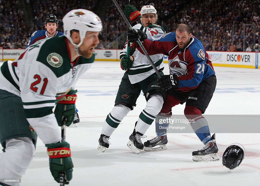 Marc-Andre Cliche #24 of the Colorado Avalanche looses his helmet as he collides with Nino Niederreiter #22 of the Minnesota Wild in Game Two of the First Round of the 2014 NHL Stanley Cup Playoffs at Pepsi Center on April 19, 2014 in Denver, Colorado. The Avalanche defeated the Wild 4-2 to take a 2-0 game lead in the series.