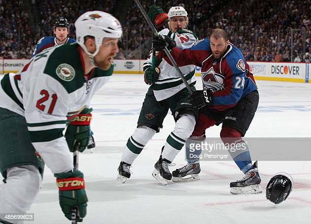 MarcAndre Cliche of the Colorado Avalanche looses his helmet as he collides with Nino Niederreiter of the Minnesota Wild in Game Two of the First...
