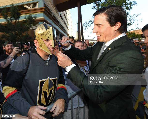 MarcAndre Fleury of the Vegas Golden Knights autographs a homemade mask for Luc Roy of Nevada as Fleury arrives at the team's inaugural regularseason...