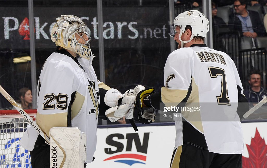Marc-Andre Fleury #29 and Paul Martin #7 of the Pittsburgh Penguins celebrate the teams win over the Toronto Maple Leafs during NHL game action October 11, 2014 at the Air Canada Centre in Toronto, Ontario, Canada.