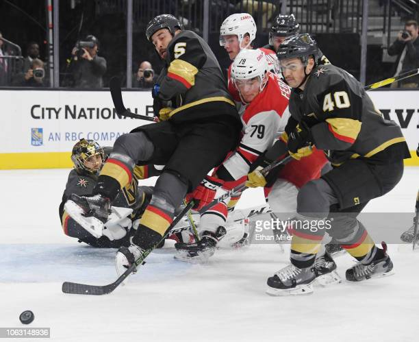 MarcAndre Fleury Deryk Engelland and Ryan Carpenter of the Vegas Golden Knights defend the net against a shot by Micheal Ferland of the Carolina...