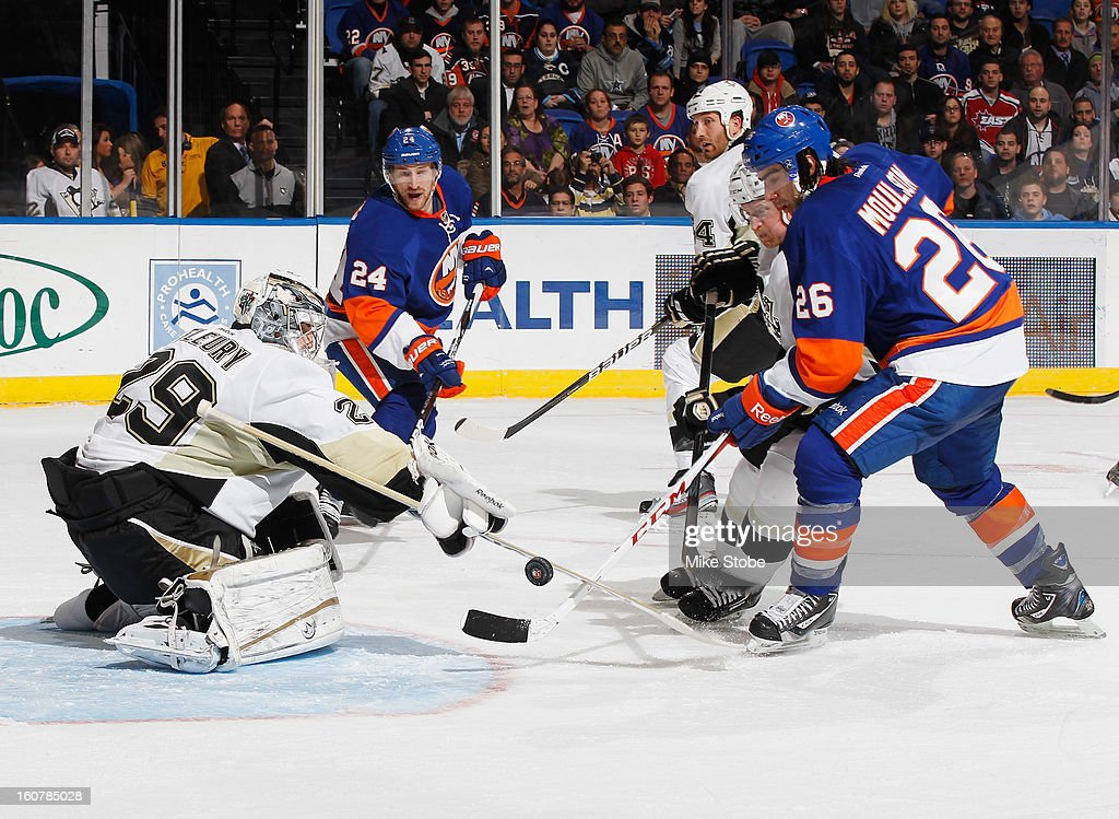Marc-Andre Fleury #29 of the Pittsburgh Penguins defends the net against Brad Boyes #24 and Matt Moulson #26 of the New York Islanders at Nassau Veterans Memorial Coliseum on February 5, 2013 in Uniondale, New York. The Penguins defeated the Islanders 4-2.