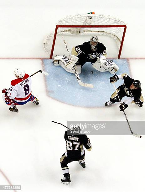 MarcAndre Fleury of the Pittsburgh Penguins keeps an eye on a airborne puck against Alex Ovechkin of the Washington Capitals during the game at...