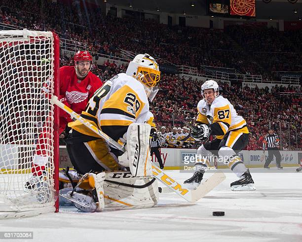 MarcAndre Fleury of the Pittsburgh Penguins makes a save as teammate Sidney Crosby defends against Drew Miller of the Detroit Red Wings during an NHL...