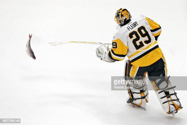 MarcAndre Fleury of the Pittsburgh Penguins scoops up a catfish in warmups prior to the game against the Nashville Predators in Game Three of the...