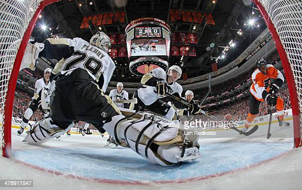 MarcAndre Fleury of the Pittsburgh Penguins slides across his crease as teammte Olli Maatta defends against Wayne Simmonds of the Philadelphia Flyers...