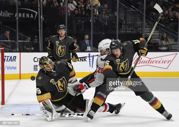 MarcAndre Fleury of the Vegas Golden Knights blocks a shot as Lars Eller of the Washington Capitals and Jon Merrill of the Golden Knights battle in...