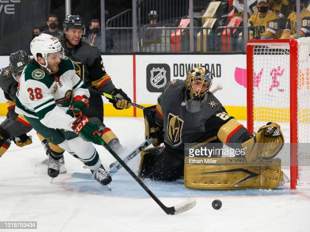 Marc-Andre Fleury of the Vegas Golden Knights defends the net against Ryan Hartman of the Minnesota Wild as Brayden McNabb of the Golden Knights...